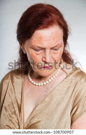 Portrait of good looking senior woman with expressive face showing emotions. Thinking and hoping. Acting young. Studio shot isolated on grey background. - stock photo