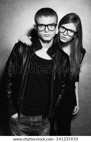 Portrait of gorgeous blond fashion twins in black clothes wearing trendy glasses & posing over silver metal  background together. Perfect hair. Natural make-up. Perfect skin. Black & white studio shot - stock photo