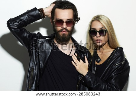 Portrait of gorgeous fashion beautiful couple in black clothes wearing trendy glasses and posing over white background together. Hipster boy and girl. Bearded young man and blonde in sunglasses - stock photo