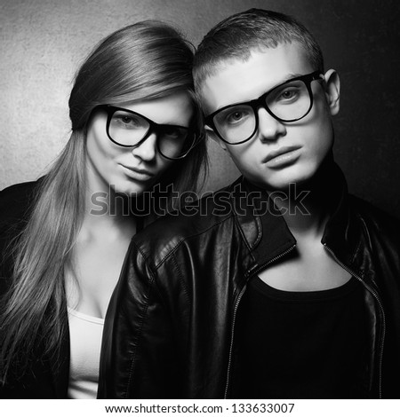 Portrait of gorgeous fashion twins in black clothes wearing trendy glasses and posing over gray background together. Perfect hair. Natural make-up. Perfect skin. Hipster style. Monochrome studio shot. - stock photo