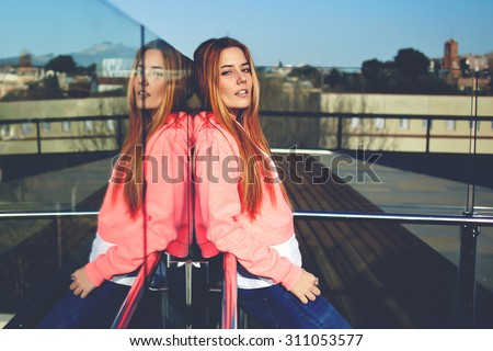 Portrait of gorgeous hipster girl dressed in trendy clothing enjoying the beautiful sunny day outdoors, fashionable young woman with luxurious long hair posing outside in summer while looking at you - stock photo
