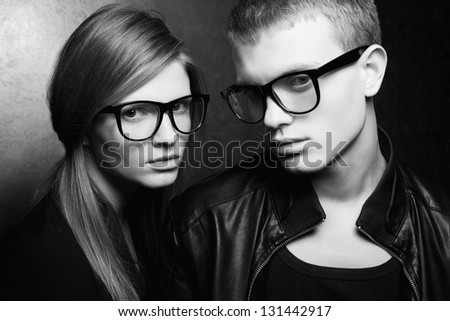 Portrait of gorgeous red-haired fashion twins in black clothes wearing trendy glasses and posing over metal background. Perfect hair and skin. Natural make-up. Hipster style. Studio shot. - stock photo