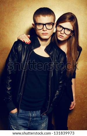 Portrait of gorgeous red-haired fashion twins in black clothes wearing trendy glasses and posing over golden background together. Perfect hair. Natural make-up. Perfect skin. Studio shot. - stock photo