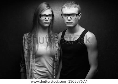 Portrait of gorgeous red-haired fashion twins in casual shirts wearing trendy glasses and posing over golden background together. Black and white (monochrome) studio shot. - stock photo
