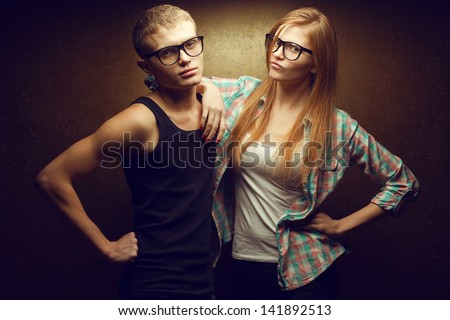 Portrait of gorgeous red-haired (ginger) fashion twins in casual shirts wearing trendy glasses and posing over golden background together. Studio shot - stock photo