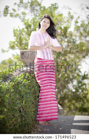 Portrait of gorgeous young burmese woman with the traditional dress and showing respect - stock photo