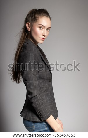 Portrait of gorgeous young caucasian attractive sexy business woman or secretary wearing checked jacket and jeans - stock photo