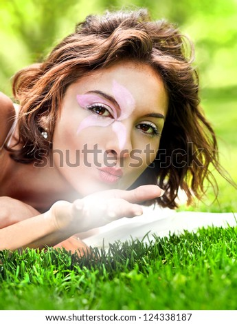 Portrait of Gorgeous young pretty brunette woman relaxing in sunny spring park in white cloth with beautiful curly hair on bright green grass laying and sending a kiss - stock photo