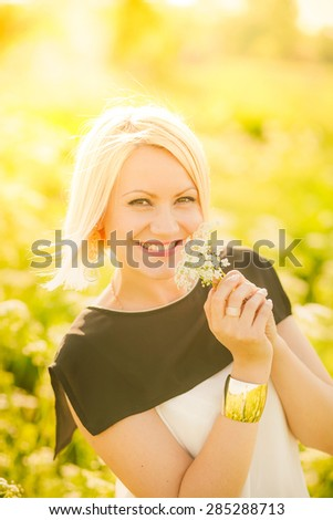 Portrait of gorgeous young woman in sunlight outside. Sunset people. Happy girl enjoying nature in summer meadow. Charming free blonde standing in sunny garden. Close up of beautiful smiling face. - stock photo