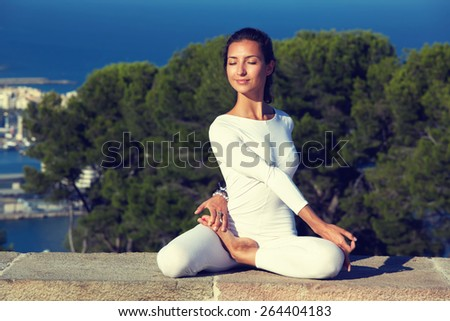 Portrait of gorgeous young woman practicing yoga on a sunny day with amazing sea view from high altitude, woman seeking enlightenment through meditation, relaxed girl performing yoga routine, filter - stock photo
