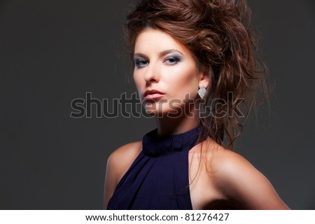 portrait of graceful young woman with hairstyle over dark background - stock photo