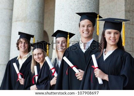 Portrait of graduates posing in single line with columns in background - stock photo