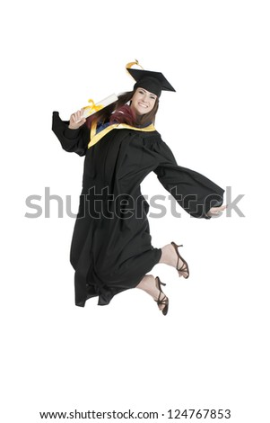 Portrait of graduating student jumping for joy against white background - stock photo