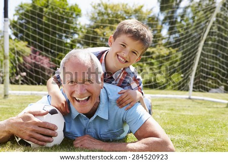 Portrait Of Grandfather And Grandson With Football - stock photo