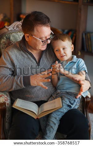 Portrait of Grandfather talking to his small grandson about the book - stock photo