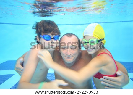 Portrait of grandfather with boy and girl under water in the swimming pool  - stock photo