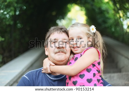 Portrait of grandfather with granddaughter outdoor - stock photo