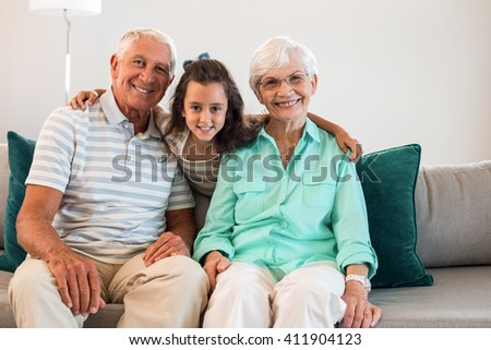 Portrait of grandmother and grand father with their granddaughter sitting on sofa in living room - stock photo