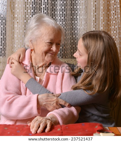 Portrait of grandmother and granddaughter at home - stock photo