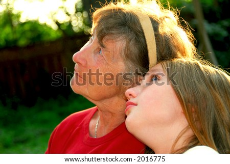 Portrait of grandmother and granddaughter in summer park looking up - stock photo