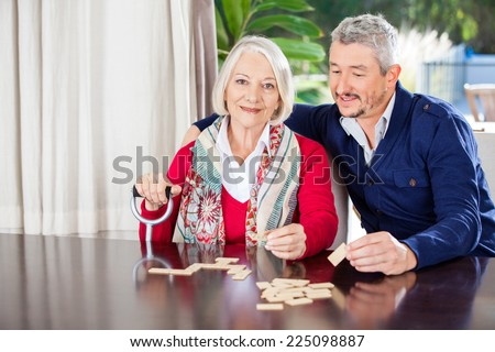 Portrait of grandmother holding walking stick while playing dominoes with grandson at nursing home - stock photo