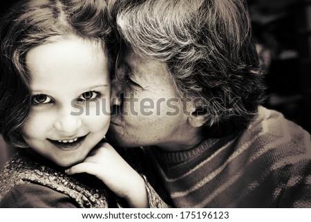 Portrait of Grandmother kissing her granddaughter. - stock photo