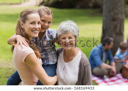 Portrait of grandmother, mother and daughter with family in background at the park - stock photo