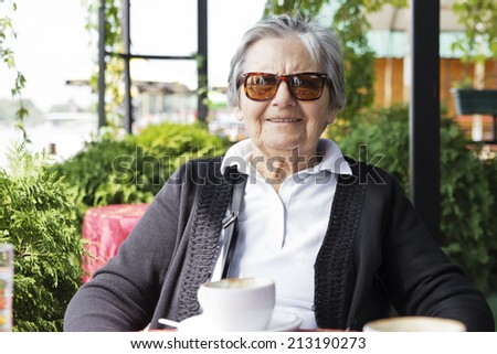 Portrait of grandmother wearing a sunglasses sitting in the restaurant.	  - stock photo
