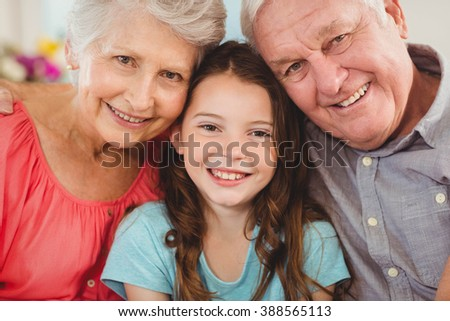 Portrait of grandparents and granddaughter sitting together on sofa in living room - stock photo