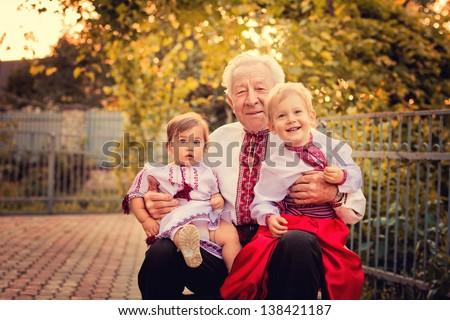 Portrait of grandparents with grandchildren in Ukrainian costume at sunset - stock photo