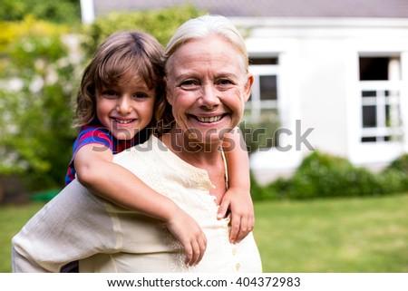 Portrait of granny piggybacking grandson in yard - stock photo