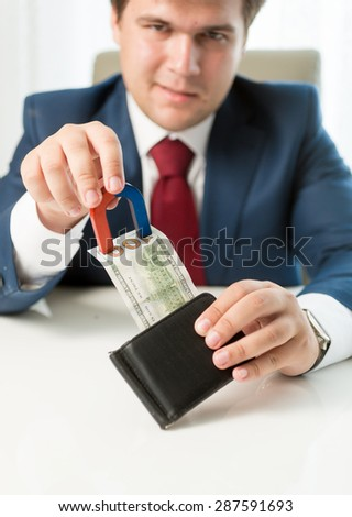 Portrait of greedy businessman pulling money out wallet with use of magnet - stock photo