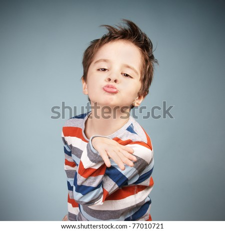 Portrait of grimacing little boy blowing a kiss, studio shot - stock photo