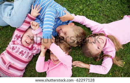 portrait of group children playing on the grass - stock photo