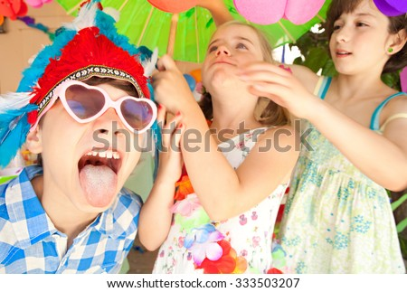 Portrait of group of children friends at a birthday party with boy pulling faces and sticking tongue out, dressing up in colorful fancy dresses, joyful together. Kids active lifestyle in home garden. - stock photo