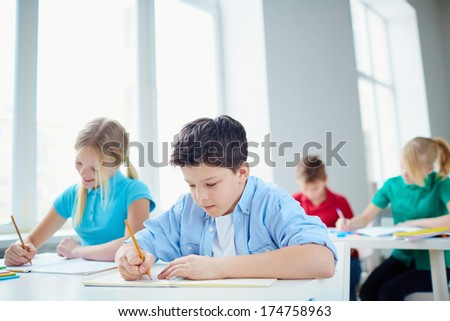 Portrait of group of diligent pupils drawing at lesson - stock photo