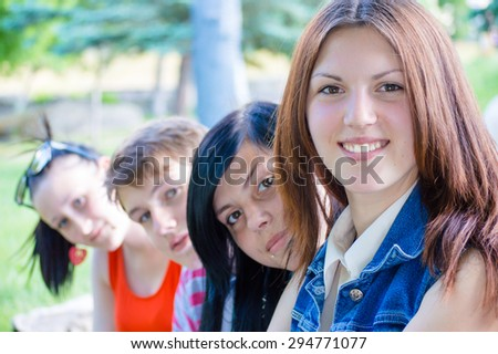 Portrait of group of four young people looking at camera on outdoors background - stock photo
