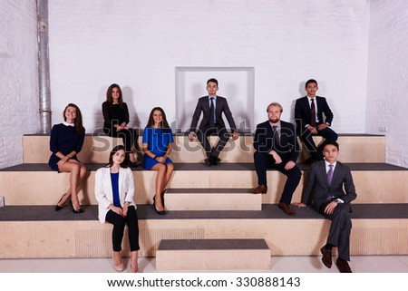 Portrait of group of young successful business people dressed in elegant clothes resting after briefing, intelligent international students resting after lectures while sitting in University audience - stock photo