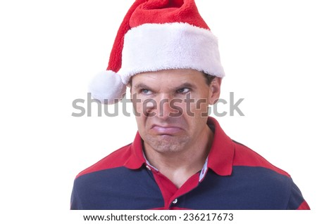 Portrait of grumpy Caucasian man wearing casual shirt and red Santa hat making ugly grinch face on white background - stock photo