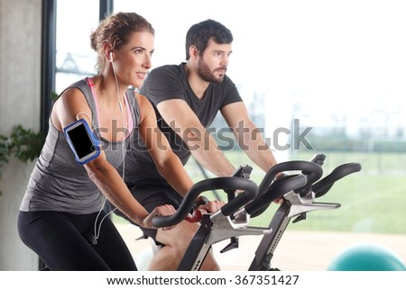 Portrait of gym members participating in a spinning class while training together at fitness center. Sporty woman listening music at her mobile phone.  - stock photo