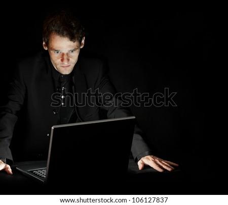 Portrait of hacker with laptop on dark background - stock photo