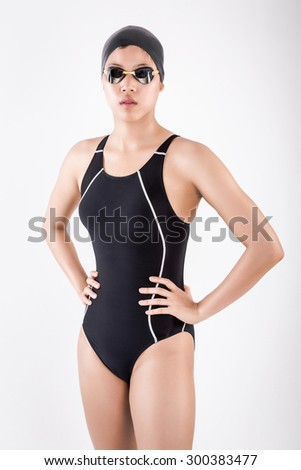 portrait of half body young female swimmer in blue swimsuit with goggle and swimming hat. akimbo posing in studio set white background - stock photo