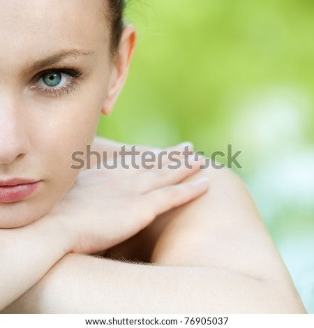 portrait of half face young woman on green background - stock photo