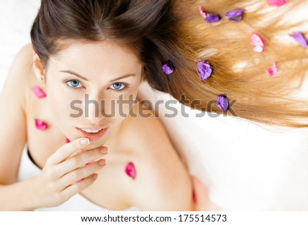 Portrait of half-naked woman lying in petals of flowers. Concept of beauty and youth - stock photo