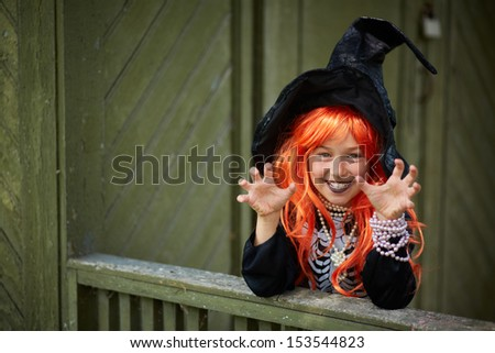 Portrait of Halloween girl with red hair wearing black hat - stock photo