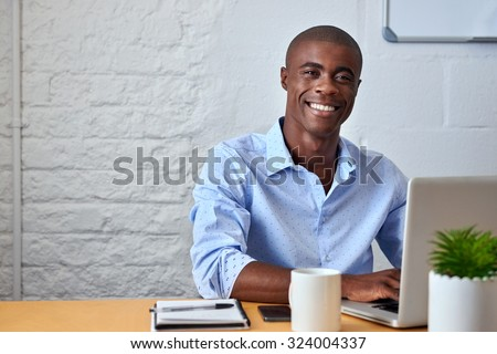 portrait of handsome African black young business man working on laptop computer at office desk - stock photo