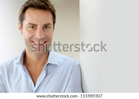 Portrait of handsome and happy guy leaning on wall - stock photo