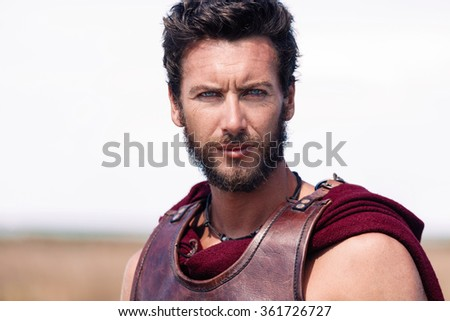Portrait of handsome and proud ancient warrior in armor. Spartan Soldier. Landscape background - stock photo