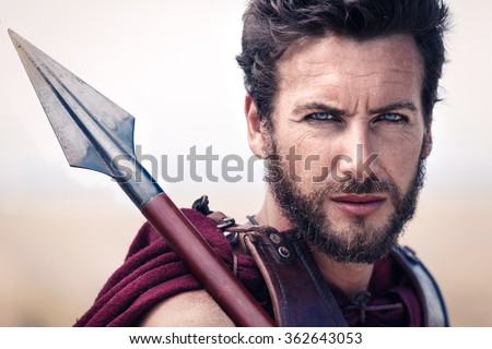 Portrait of handsome and proud ancient warrior in armor with spear. Spartan Soldier. Landscape background - stock photo