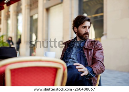 Portrait of handsome and stylish man with beard enjoying a cup of coffee in a coffee shop, adult fashionable hipster having coffee in beautiful cafe terrace - stock photo